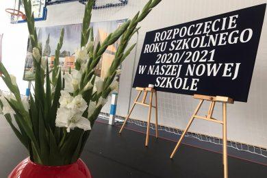 """zdjęcie wazono z kwiatami obok, którego ustawiona jest tablica z napisem """"ROZPOCZĘCIE ROKU SZKOLNEGO 2020/2021 W NASZEJ NOWEJ SZKOLE"""""""