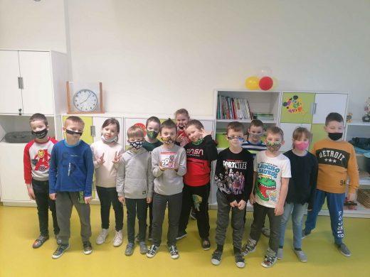 Uczniowie stoją w rzędzie w swojej klasie na tle zielono białych mebli.