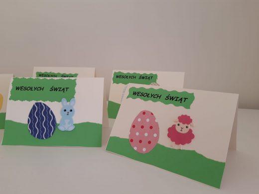 """Na stoliku ustawiono cztery kartki świąteczne. Na dwóch z pierwszego planu widać napis na zielonym tle """"Wesołych Świąt"""" , naklejone pisanki oraz wielkanocne zwierzątka."""