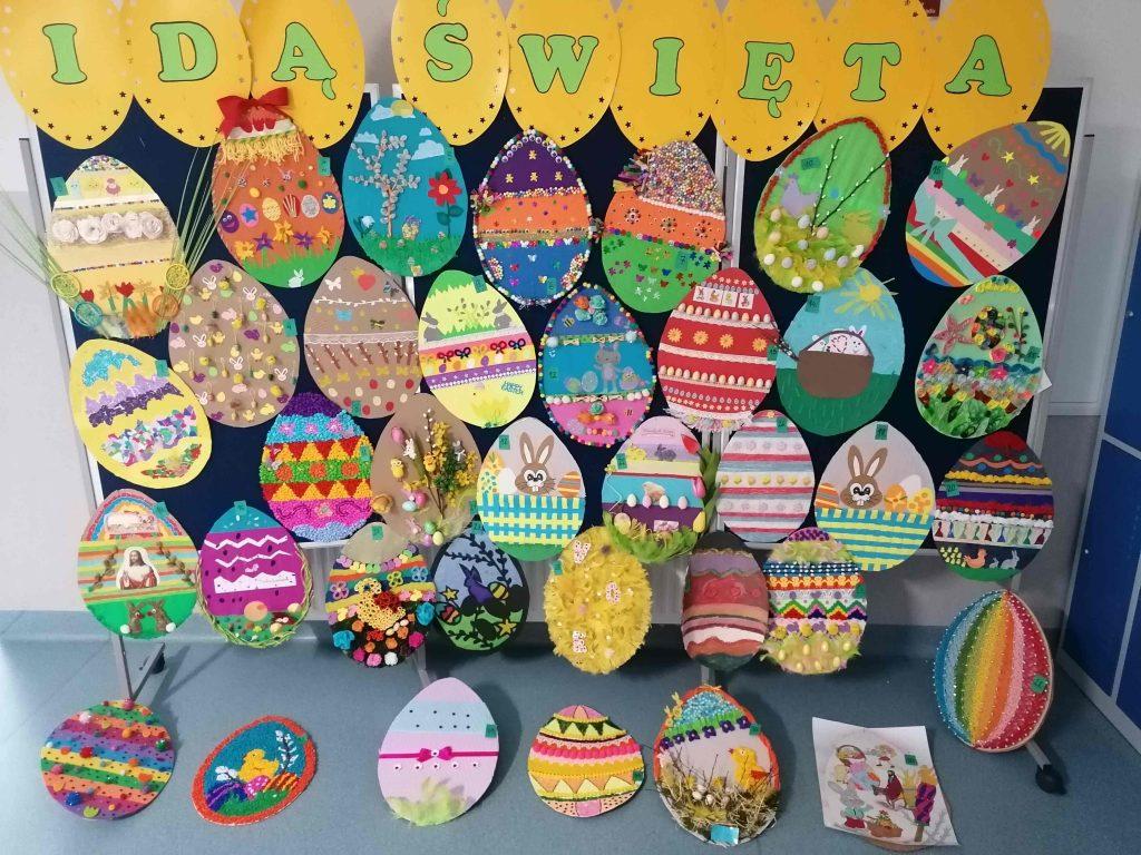 """Zdjęcie tablicy z przyczepionym napisem """"IDĄ ŚWIĘTA"""" i umieszczonymi pod nimi papierowymi jajkami wykonanymi przez uczniów na konkurs."""