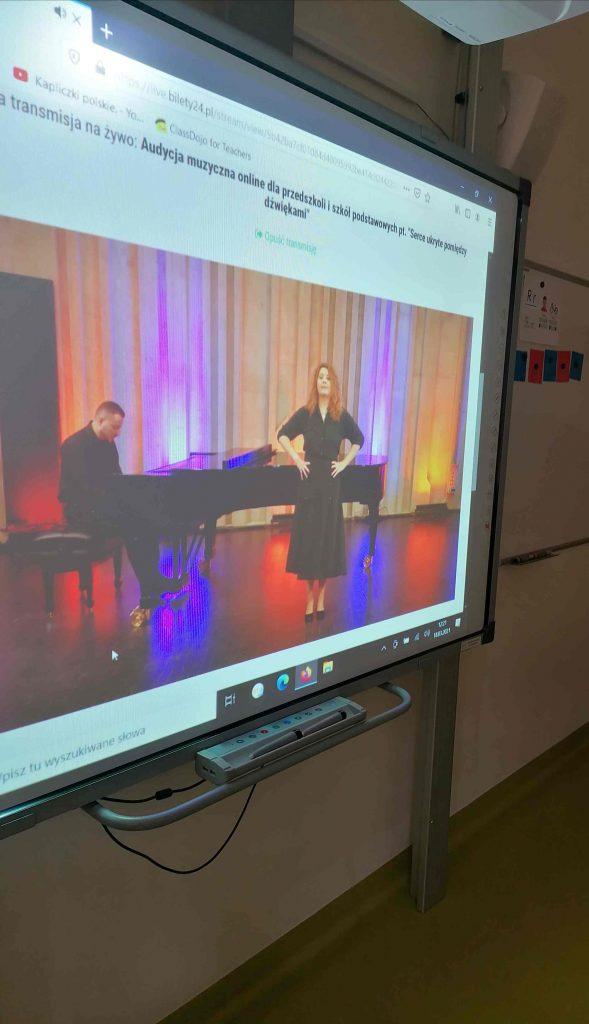 Zdjęcie tablicy interaktywnej, na której wyświetlona jest audycja muzyczna - mężczyzna gra na fortepiania, przy którym stoi kobieta.