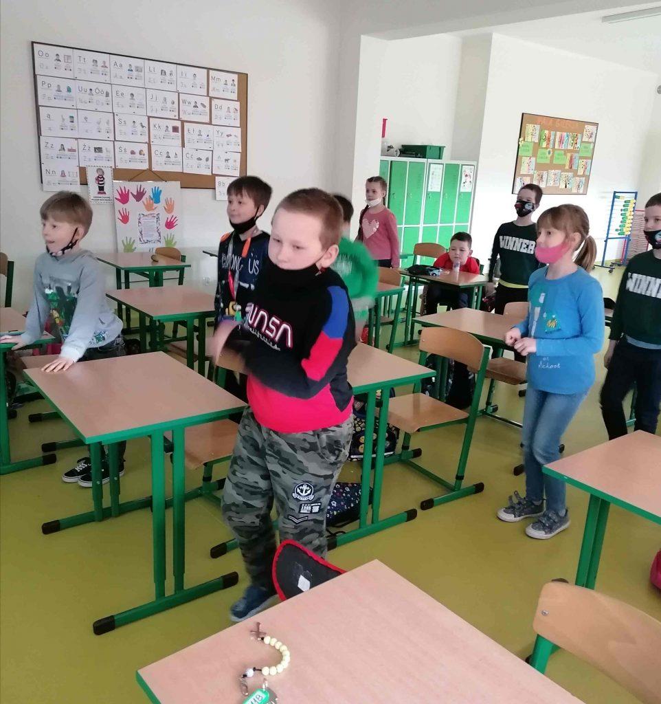 Zdjęcie zrobione w klasie szkolnej. Przy jednoosobowych ławkach stoją uczniowie.