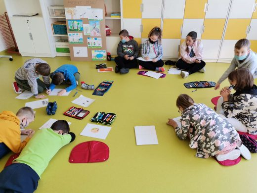 Zdjęcie przedstawia uczniów siedzących lub leżących na podłodze sali lekcyjnej. Przed nimi leżą kartki i piórniki.