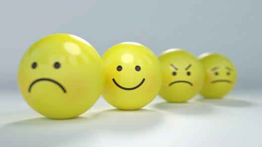 Zdjęcie przedstawia ustawione w rzędzie cztery żółte kule, na których narysowane miny przedstawiające różne emocje.