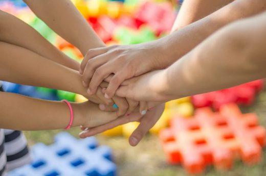 Zdjęcie przedstawia dziecięce dłonie, które nakładają sie na siebie.