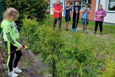 Uczennica podlewa świeżo zasadzone drzewka. Na drugim planie stoją uczniowie oparci o łopaty wraz z dwojgiem rodziców.