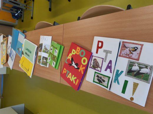 Zdjęcie przedstawia dwie złączone ławki na których ułożono lapbooki o ptakach wykonane przez uczniów.