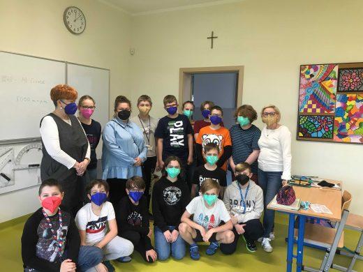 Zdjecie grupowe - uczniowie w otrzymanych maseczkach, ich nauczycielka, Pani Dyrektor i przedstawicielka firmy Sohbi Craft Poland, pozują wspólnie do zdjęcia w sali lekcyjnej.