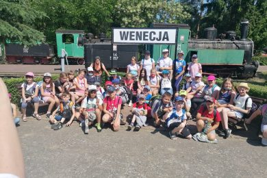 """Uczestnicy wycieczki pozują wspólnie do zdjęcia pod tablicą z napisem """"WENECJA"""". W tle stoi zabytkowy pociąg."""