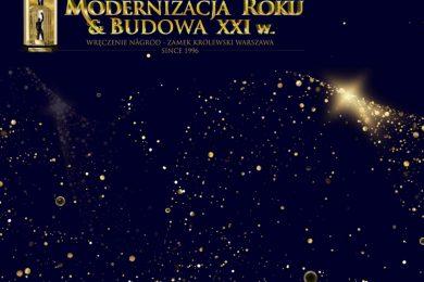 """Grafika przedstawia złote kropki przypominające gwiazdy umieszczone na granatowym tle, a nad nimi mnapis: """"OGÓLNOPOLSKI KONKURS OTWARTY MODERNIZACJA ROKU & BUDOWA XXI W. WRĘCZENIE NAGRÓD - ZAMEK KRÓLEWSKI WARSZAWA SINCE 1996""""."""