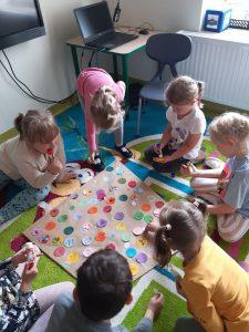 Dzieci klęczą na kolorowym dywanie i przyklejają papierowe kółka do tworzonego przez nich dużego latawca.
