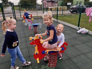 Trzy uczennice bawią się na placu zabaw. Dwie z nich siedzą na bujanym koniku.