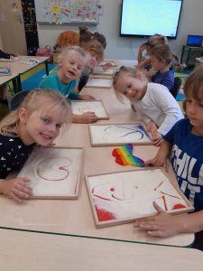 Dzieci z zerówki siedzą przy długim stole. Przed nimi leżą ich prace wykonane palcami w mące.