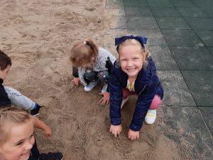 Dziewczynki z zerówki bawią się w piasku. Dziewczynka z pierwszego planu szeroko uśmiecha się do aparatu.