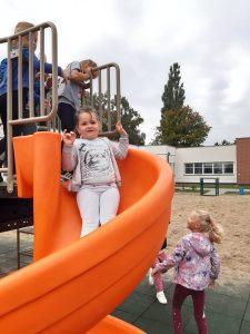 Uczniowie zerówki bawią się na placu zabaw. Na pierwszym planie dziewczynka zjeżdża na pomarańczowej zjeżdżalni i patrzy się w stronę aparatu.