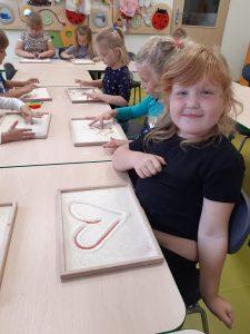 Zdjęcie uczniów przy pracy - w ramkach z mąką rysują palcami różne kształty. Dziewczynka z pierwszego planu ma już wykonany obrazek serca i patrzy się z uśmiechem w obiektyw.