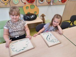 Dwie uczennice zerówki pozują do zdjęcia siedząc przy stoliku. Przed nimi leżą ich prace wykonane palcami - w drewnianej ramce z mąką.