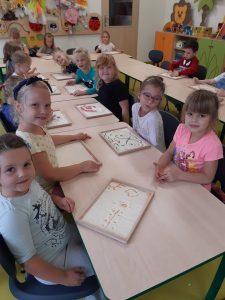 Zdjęcie przedstawia salę zerówki, w której przy stoliku w kształcie litery u siedzą uczniowie. Przed nimi leżą ich prace wykonane z mąki.