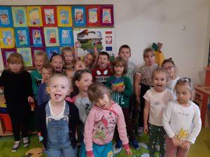 Uczniowie zerówki pozując do zdjęcia robią różne miny - część z uczniów wytyka język a inne się uśmiechają. W tle widoczna jest ściana z kolorowymi pracami uczniów.