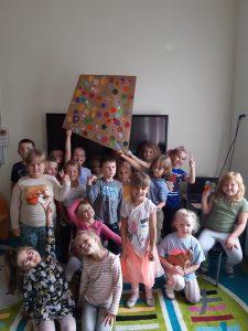 Dzieci z zerówki pozują do zdjęcia w swojej klasie. Uczniwoie stojący z tyłu trzymają w wyciągniętych dłoniach wspólnie wykonanego latawca.