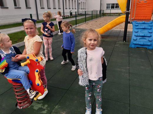 Uczniowie zerówki bawią się na placu zabaw.