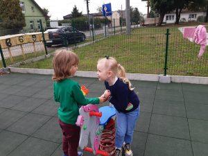Dwie uczennice zerówki bawią się na placu zabaw przy bujanym koniku.