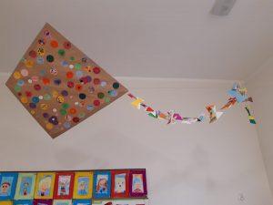Zdjęcie kolorowego latawca wykonanego przez uczniów zerówki zawieszonym nad sufitem sali.