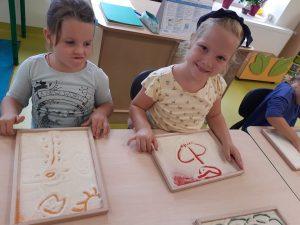 Dwie uczennice zerówki siedzą przy stoliku. Przed nimi leżą ich prace z mąki wykonane palcami. Jedna z dziewczynek uśmiecha się do zdjęcia a druga spogląda na jej pracę.