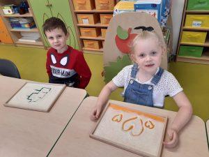 Dwoje uczniów zerówki siedzi przy stoliku. Przed nimi leżą ich prace z mąki wykonane palcami. Uczniwoie patrzą w obiektyw aparatu.
