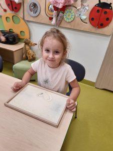 Uczennica zerówki siedzi uśmięchnięta przy stoliku. Przed nią leży ramka wypełniona mąką, w której dziewczynka narysowała serduszko.