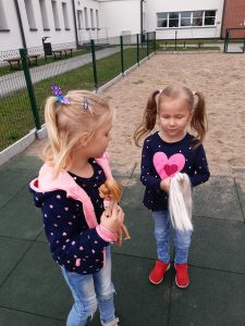 Dwie uczennice zerówki pozują do zdjęcia na placu zabaw, trzymajac w dłoniach swoje lalki barbie.