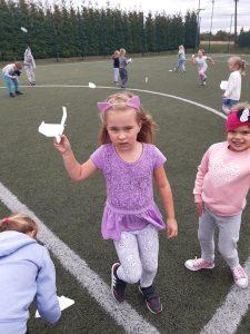 """Uczniowie zerówki biegają po szkolnym """"Orliku"""". Na pierwszym planie uczennica w opasce z różowymi uszkami trzyma w podniesionej dłoni papierowy samolocik."""