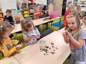 Dzieci z oddziału przedszkolnego oglądają pod lupami różne przedmioty. Na pierwszym planie widzimy dziewczynki trzymające lupy w dłoniach a przed nimi na stoliku leżą rozsypane kamyczki oraz pusty słoik.