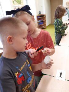 Dwoje uczniów z odziału przedszkolnego stoi obok siebie. trzymając w ręku muszelkę. Dziewczynka pokazuje chłopcu jak jej muszelka wygląda przez lupę.