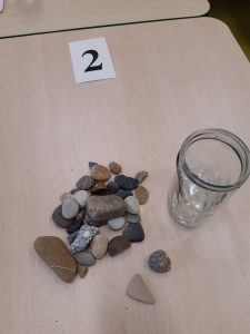 Na stoliku obok pustego słoika leżą kamienie oraz karteczka z numerem 2,