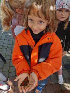 Dziwczynka z oddziału przedszkolnego pozuje do zdjęcia trzymając w złączonych ze sobą dłoniach motylka.