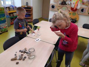 Przy stoliku na którym leżą rozrzucone kamienie, pusty słoik i karteczka z numerem 2 stoi dwójka uczniów oddziału przedszkolnego. Oboje trzymają w ręku lupy oraz przedmioty, które przez nie oglądają.