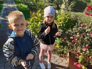 Dziewczynka i chłopiec z oddziału przedszkolnego pozują do zdjęcia trzymając w dłoniach winogrona.
