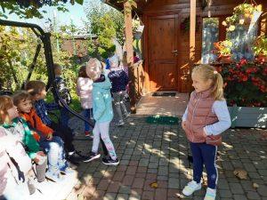 Dzieci z odziału przedszkolnego stoją przed drewnianym domkiem. Część uczniów siedzi na dużej bujanej ławce.