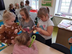 Uczniowie z oddziału przedszkolnego stoją dwóch grupkach i oglądają przez lupy różne drobne przedmioty.