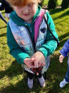 Uczennica oddziału przedszkolnego ma złożone dłonie a na jednym z jej palców siedzi motylek.