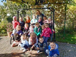 Dzieci z oddziału przedszkolnego wraz z wychowawczynią pozują do zdjęcia przy dużej bujanej ławce.