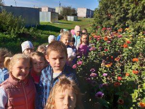 Dzieci z oddziału przedszkolnego pozują do zdjęcia przy grządce porpśniętej kwiatami. W tle widoczne są pojedyncze zabudowania.