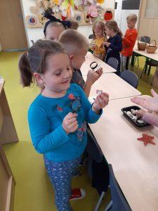 Uczniowie z oddziału przedszkolnego oglądają różne przedmioty przez lupy, które trzymają w dłoni. Dziewczynka z pierwszego planu uśmiecha się zerkając na mała muszelkę.