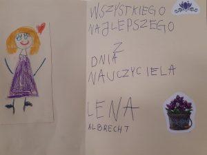 """Zdjęcie odręcznie wykonanej kartki dla Wychowawczyni Oddziału Przedszkolnego. Po lewej stronie wklejono rysunek przedstawiajacy Wychowawczynię a po prawej stronie napis:""""WSZYSTKIEGO NAJLEPSZEGO Z DNIA NAUCZYCIELA LENA ALBRECHT"""". Kartkę dodatkowo udekorowano dwoma naklejkami - kwiatka oraz doniczki z kwiatkami."""