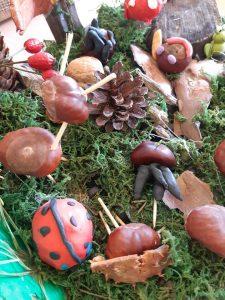 """Praca wykonana na szkolny konkurs """"Makieta jesiennego lasu"""" - na podstawie z mchu umieszczono kasztanowych ludków oraz figurki z plasteliny."""