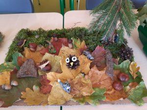 """Praca wykonana na szkolny konkurs """"Makieta jesiennego lasu"""" -na tekutze umieszczono kolorowe liści i mech a na nimch rozmieszczono kasztany, żołędzie i szyszki. Po środku położono szyszkę ozdobioną oczami i nosem,"""