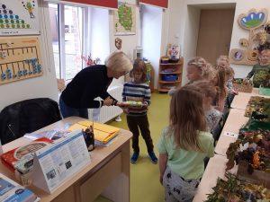 Pani Dyrektor wręcza nagrodę uczniowi z oddziału przedszkolnego. Koleżanki stojące obok przyglądają się tej scenie.