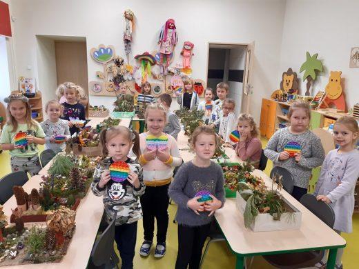 Uczniwoie z oddziału przedszkolnego stoją między ławkami na których umieszczono ich prace konkursowe. Dzieci trzymają w dłoniach swoje nagrody - kółka push pop.