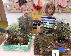 Dwóch uczniów stoi przed swoimi pracami konkursowymi. W dłoniach trzyma nagrody - kółka push pop.